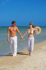 happy couple at the beach walking