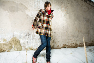 young girl pose in wool topcoat before a facture wall