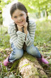 Young girl sitting on log