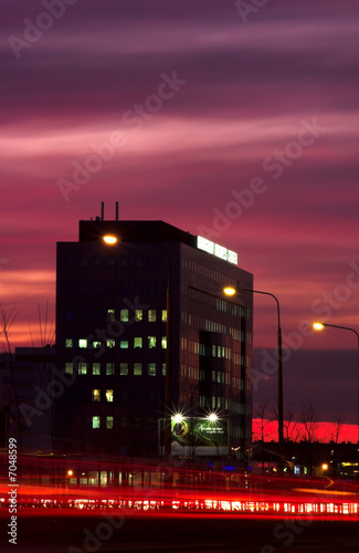 Business building in sunset with blurred traffic lights