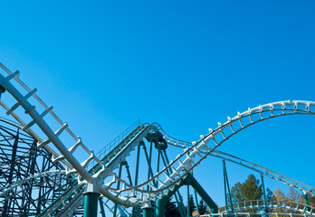 Curved roller coaster construction at blue sky