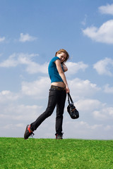 The young attractive girl with a bag on a background of the blue