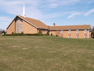 modern rural brick church by a grass lawn