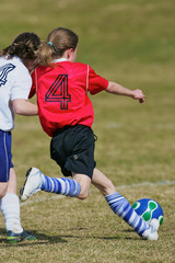 Two girls running to the soccer ball during a game