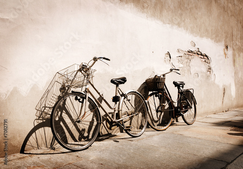 Italian old-style bicycles leaning against a wall  - 7082791