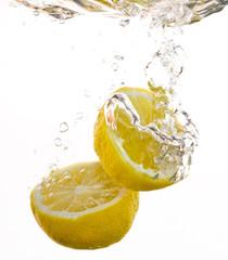 2 Hälften von Zitronen fallen ins Wasser und machen Blasen