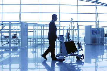 Geschäftsmann mit Gepäckwagen im Terminal