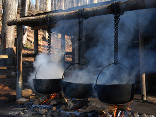 making maple syrup by boiling the sap in a cauldron