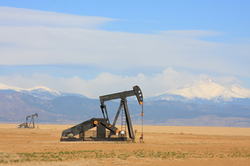 Pumpjack pumping oil, snow capped mountain background