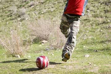 Men teens playing soccer in green grass