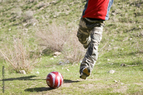 Men teens playing soccer in green grass