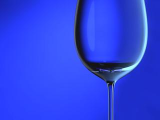Leeres Weinglas vor blauem Hintergrund