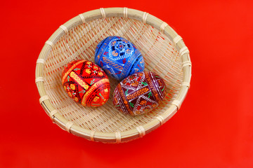 three russian tradition easter eggs in yellow basket over red