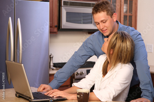 young couple with a laptop on a kitchen