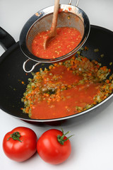 Pressing cooked tomatoes through a strainer in pan