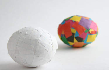Two eggs, with glued bits of colour and white paper