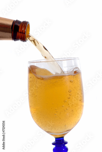 Bottle of cold beer filling the glass