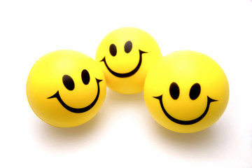 Three smiley faces over white