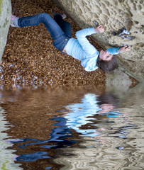 A girl climbs on a rock above water