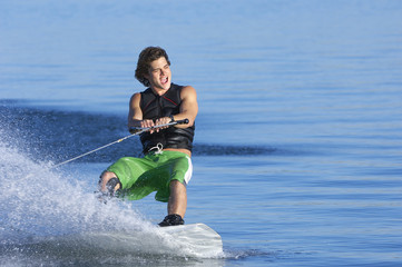 Young man wakeboarding on lake