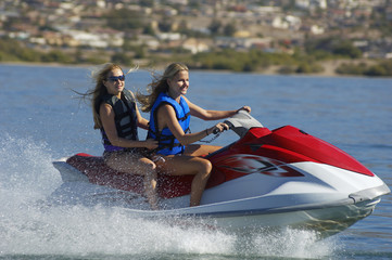 Two young women riding jetski on lake