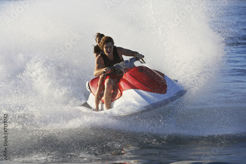 Young couple riding jetski on lake