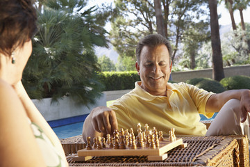 Man and woman playing chess by swimming pool