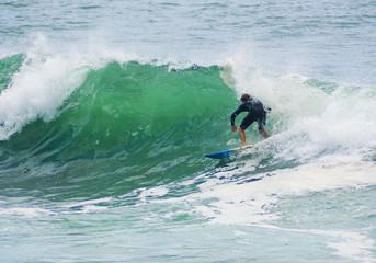 surfer surfs big wave