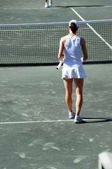 tennis player walking towards net