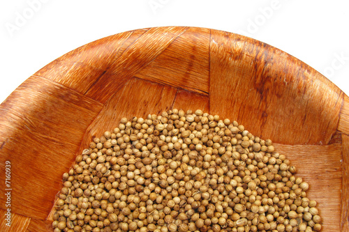 Coriander dried seeds in wooden dish
