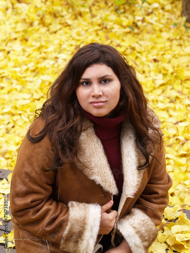 Young Woman in Jacket with Yellow Leaves Background