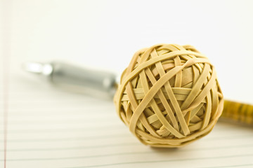 Rubberband ball and pen on notebook paper