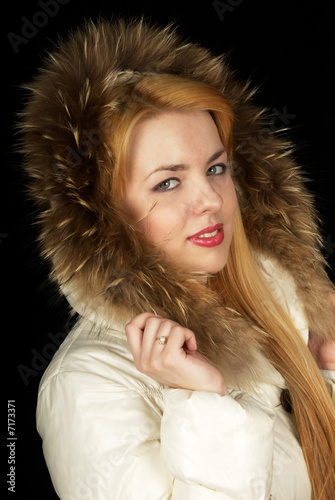Teen-age girl in jacket on black background.