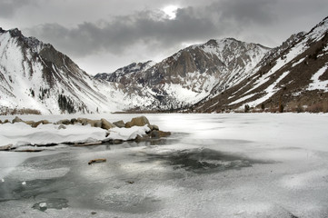 Frozen Lake and snowy mountains, cold winter day.