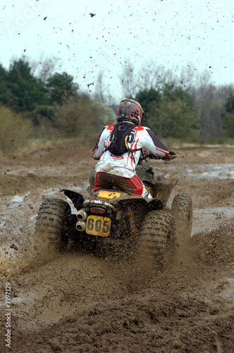 big yellow quad going through a deep mud