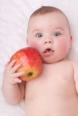 adorable baby eating red apple  over white background