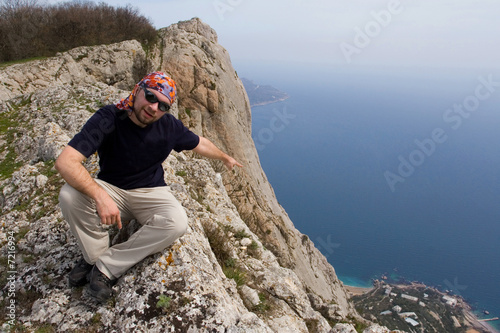 Person climbing sitting on cliff