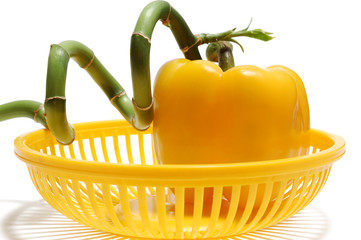 yellow paprika and green bamboo in yellow basket