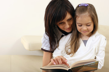 Mother reading a book to her daughter 2