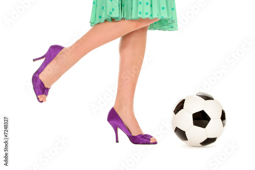 Woman with high heels kicking a soccer ball