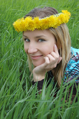 Girl with dandelion diadem over green grass