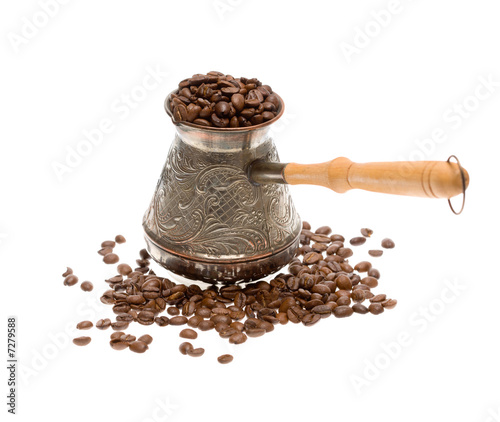 Cezve with freshly roasted coffee beans over white background