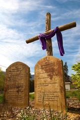 A cross with the ten commandments in stone in front of it.