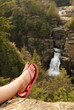 A human foot relaxing in front of waterfall.