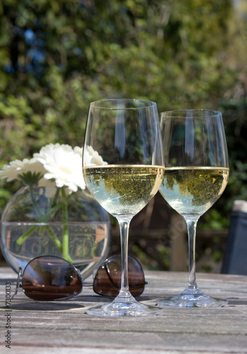 wine, sunglasses & flowers on wooden patio table