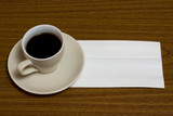 A cup of coffee with napkin on a table poster