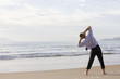 Businessman doing exercises on beach