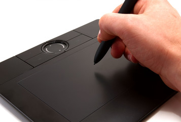 A human hand holding pen on graphic tablet for computer.