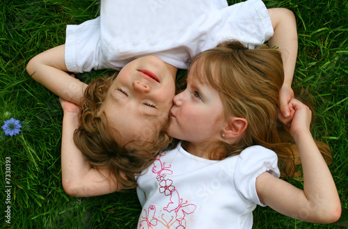 A girl kissing a boy while laying in the grass