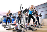 Women working out on spinning bikes at the gym - 7334135
